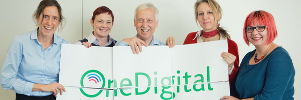 5 people holding up a signs that combine to make the One Digital logo