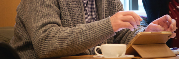 Person operating a tablet at a table, with a teacup next to them.