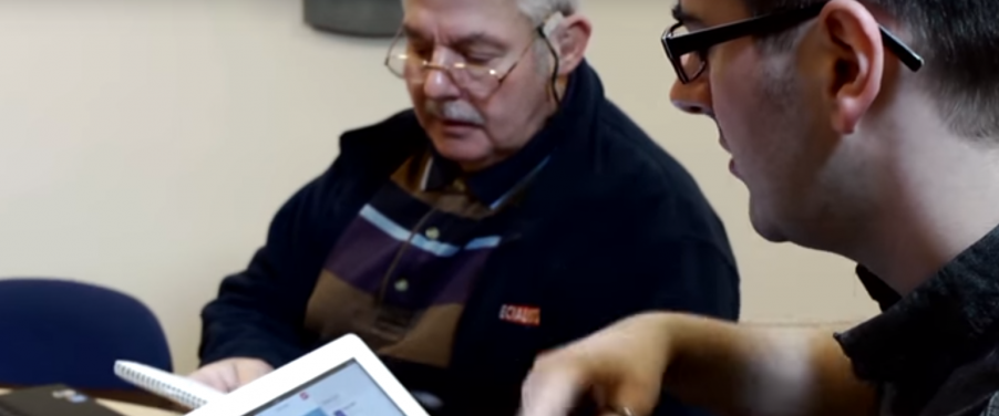 Digital Champion helping a man with a tablet