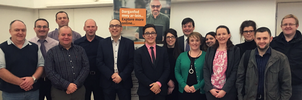 "Photo of 11 men and 5 women of various ages in suits in front of Digital Gwynedd banner reading ""explore more online"""