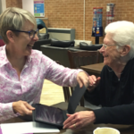 Rachel Martin and an elderly woman laughing while facing each other over a tablet, at a cafe table