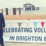 """Peter standing with banner reading """"Celebrating volunteering in Brighton & Hove"""""""