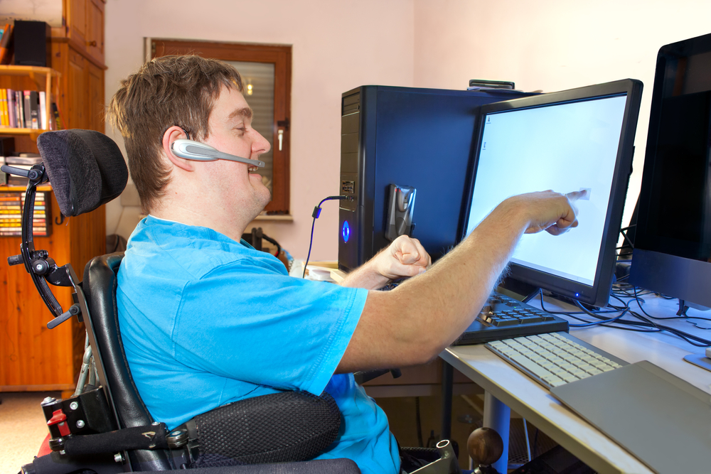 A disabled person using a computer with assistive technology. The person is pointing at or touching the computer screen.