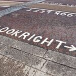 """A pedestrian showing the road markings """"Look right"""" and """"Look left"""""""